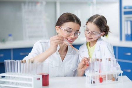 Photo pour Portrait d'une étudiante souriante regardant un professeur scientifique faire des expériences en laboratoire - image libre de droit