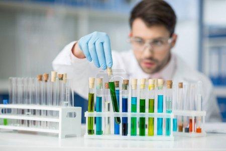 Photo pour Concentré de scientifique de l'homme en analysant les tubes à essai en laboratoire des lunettes de protection - image libre de droit