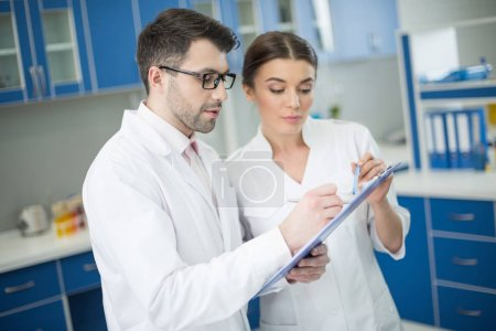 Photo for Side view of concentrated man and woman scientists writing in notepad in lab - Royalty Free Image