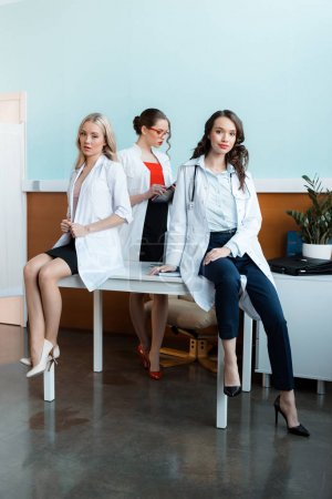 Photo for Three young medical workers in white coats sitting on table - Royalty Free Image