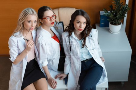 Photo for High angle view of three doctors in white coats sitting on table in cabinet - Royalty Free Image