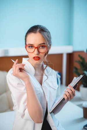 Photo for Portrait of young seductive woman in white coat and red eyeglasses holding clipboard and pen - Royalty Free Image