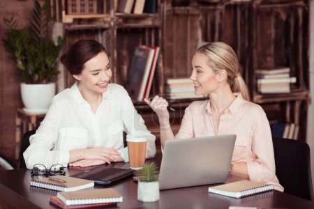Photo for Young attractive smiling businesswomen talking at desk - Royalty Free Image