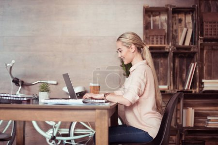 Photo for Side view of young smiling businesswoman working with laptop - Royalty Free Image
