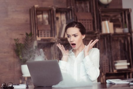Photo for Shocked young businesswoman looking at laptop with smoke - Royalty Free Image