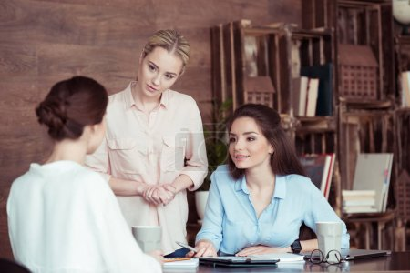 Photo for Attractive businesswomen working and discussing in office - Royalty Free Image