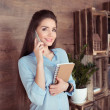 Attractive businesswoman with notebook using smart...