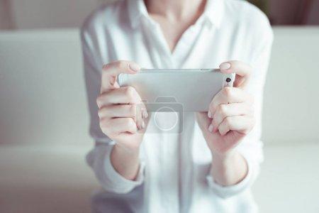 Photo pour Vue partielle de la femme tenant smartphone dans les mains - image libre de droit
