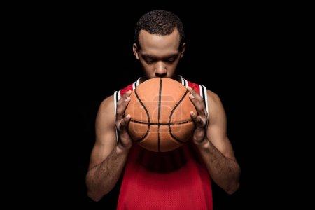 Photo pour Basketteur afro-américain posant avec balle sur noir - image libre de droit