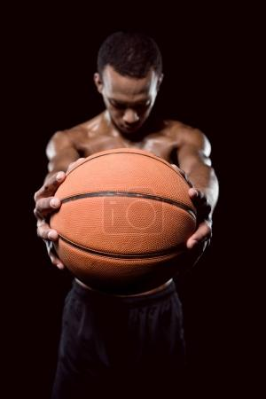 Photo for African american basketball player posing with ball on black - Royalty Free Image
