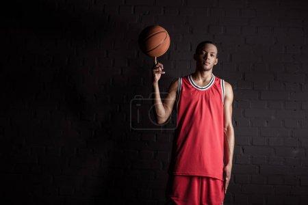 Photo pour Homme sportif africain tenant le ballon de basket sur doigt sur fond noir - image libre de droit