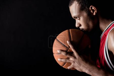 Photo for Side view of african sporty man holding basketball ball on black - Royalty Free Image