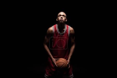 Photo pour Homme sportif africain dans les sports uniformes jouant au basketball sur fond noir - image libre de droit