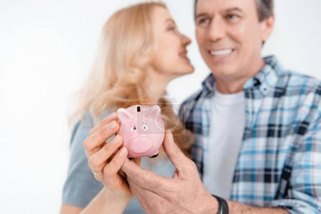 Photo pour Front view of happy couple holding piggy bank  isolated on white - image libre de droit