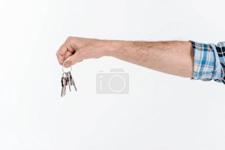 Photo pour Partial view of hand holding keys from new house  isolated on white - image libre de droit