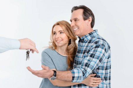 Photo for Portrait of happy couple receiving keys from new house isolated on white - Royalty Free Image