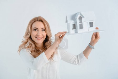 Photo for Portrait of smiling woman showing house model  isolated on grey - Royalty Free Image