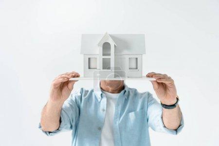 Photo pour Vue obscure de l'homme montrant modèle de maison isolé sur blanc - image libre de droit