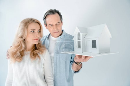 Photo for Portrait of mature couple looking at house model  isolated on grey - Royalty Free Image