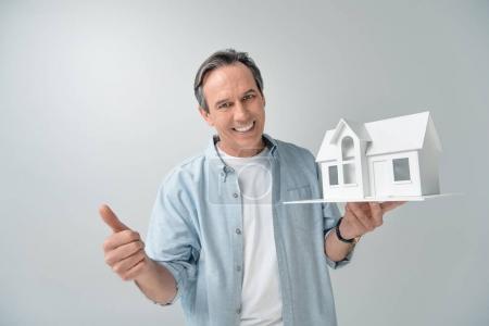 Photo pour Portrait d'homme mûr souriant avec modèle de maison montrant pouce vers le haut isolé sur gris - image libre de droit