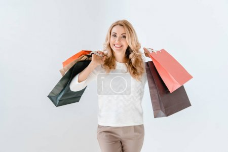 Foto de Beautiful smiling blonde woman holding shopping bags  isolated on white - Imagen libre de derechos