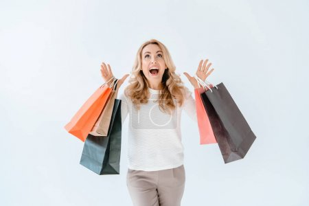Photo for Surprised blonde woman holding shopping bags and looking up isolated on white - Royalty Free Image