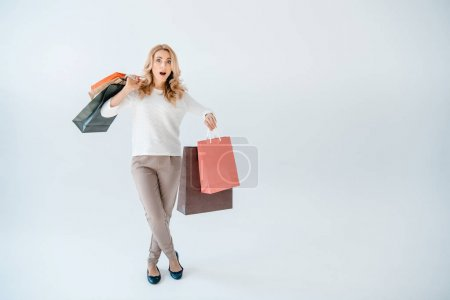 Foto de Shocked blonde woman holding shopping bags and looking at camera  isolated on white - Imagen libre de derechos