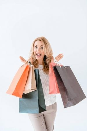 Photo for Surprised blonde woman holding shopping bags and looking at camera   isolated on white - Royalty Free Image