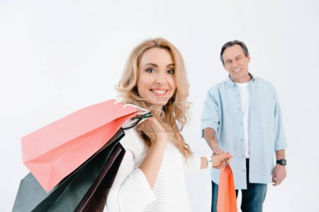 Foto de Mature man looking at happy blonde woman holding shopping bags  isolated on white - Imagen libre de derechos