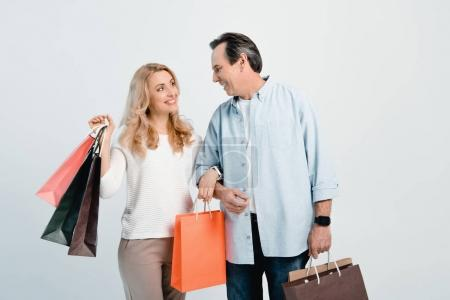 Foto de Happy middle aged couple holding shopping bags and smiling each other isolated on white - Imagen libre de derechos