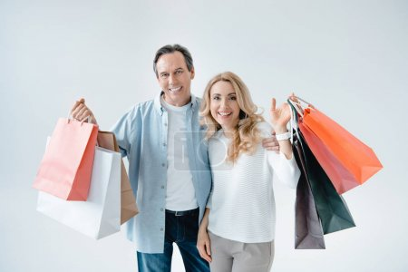 Foto de Happy middle aged couple holding shopping bags and smiling at camera   isolated on white - Imagen libre de derechos