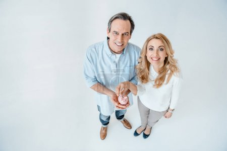 Photo pour Smiling middle aged couple putting coin into small piggy bank  isolated on white - image libre de droit