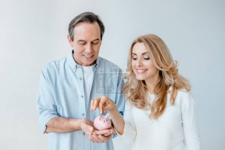 Photo pour Smiling middle aged couple putting coin into small piggy bank  isolated on grey - image libre de droit