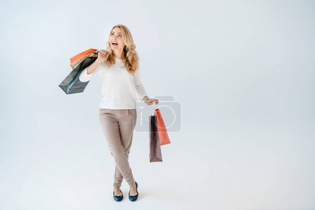 Foto de Excited beautiful woman holding shopping bags and looking up  isolated on grey - Imagen libre de derechos