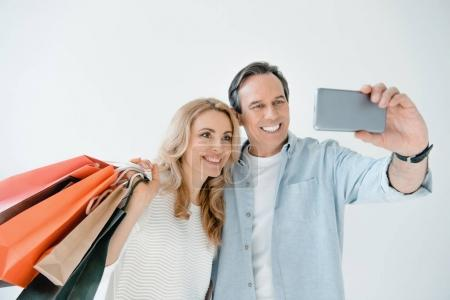 Foto de Happy couple with shopping bags taking selfie with smartphone isolated on white - Imagen libre de derechos