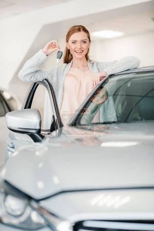 Photo pour Femme heureuse tenant la clé de voiture et debout à la voiture dans le salon de concession - image libre de droit