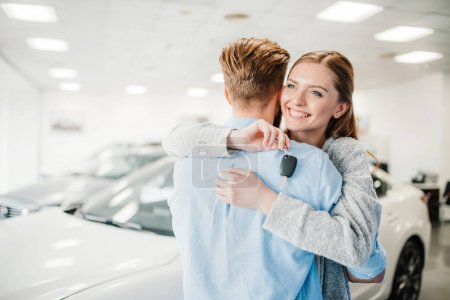 Photo for Happy couple holding car key and embracing in dealership salon - Royalty Free Image