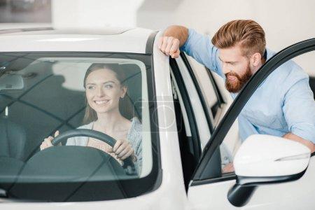 Photo pour Souriant jeune femme assise dans une nouvelle voiture et l'homme debout près - image libre de droit