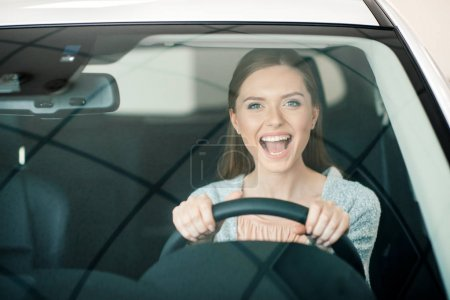 Photo for Excited young woman sitting in new car and looking at camera - Royalty Free Image