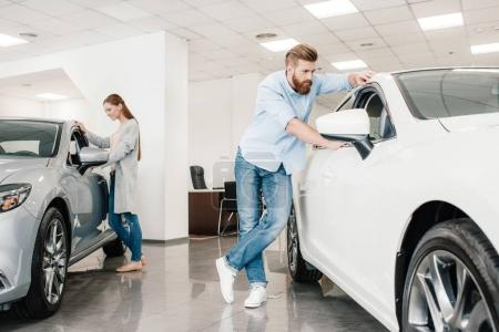 Photo for Couple choosing car, man and woman looking on various cars in dealership salon - Royalty Free Image
