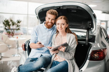 Photo for Happy couple with catalog sitting on car trunk in dealership salon - Royalty Free Image