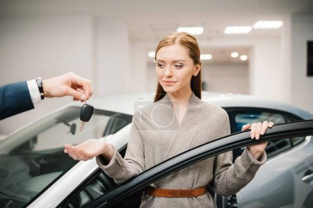 Photo for Dealer giving car key to beautiful young woman new owner - Royalty Free Image