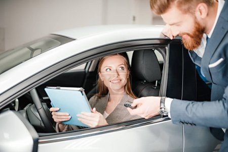 Photo for Bearded salesman giving car key to young woman sitting in new car with digital tablet - Royalty Free Image