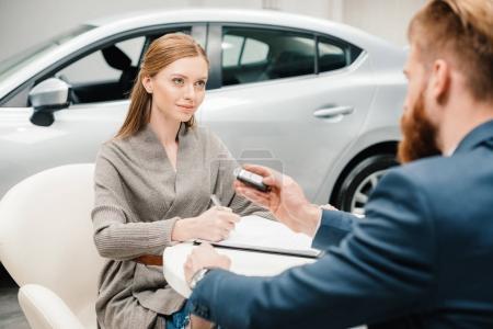 Photo pour Barbe vendeur donnant nouvelle clé de voiture à la jeune femme documents de signature - image libre de droit