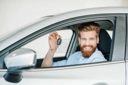 Photo for Smiling bearded young man sitting in new car and holding key - Royalty Free Image