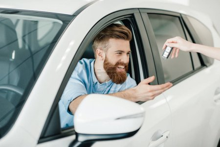 Photo for Seller giving key to happy young bearded man sitting in new car - Royalty Free Image