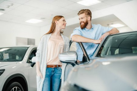 Photo for Happy young couple standing near new car and smiling each other - Royalty Free Image