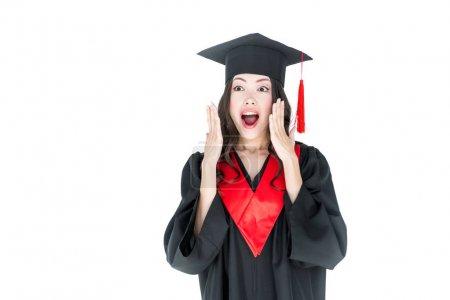 Photo pour Surpris jeune femme brune en robe de graduation et mortier isolé sur blanc - image libre de droit