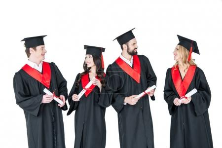 Photo pour Group of young men and women in graduation gowns and mortarboards holding diplomas isolated on white - image libre de droit