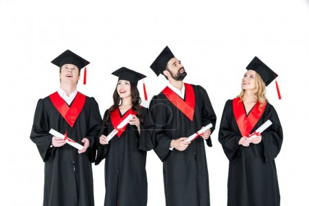 Foto de Group of young men and women in graduation gowns and mortarboards holding diplomas isolated on white - Imagen libre de derechos